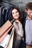 Glad woman is in the shop with boyfriend Royalty Free Stock Image