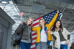 Glad women keeping banners of united states. Portrait of cheerful company of girls standing at the airport and holding up usa flag Stock Photos