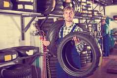 Glad working man standing with new tires Royalty Free Stock Photography