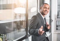 Glad young businessman is gesturing and laughing. Waist up portrait of african respectable man standng near window with wide happily smile on face. He is looking Royalty Free Stock Image