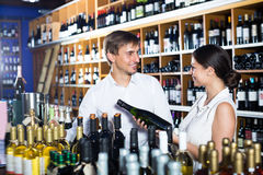 Glad young couple choosing together wine royalty free stock image