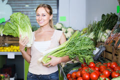 Glad young female customer holding fresh celery and leek Stock Images