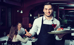 Glad young waiter taking care of adults. At cafe table Royalty Free Stock Image