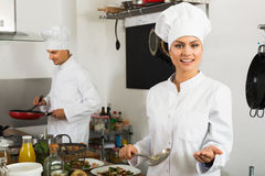 Glad young woman chef cooking food at kitchen Royalty Free Stock Images