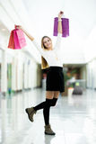 Glad young woman dancing with shopping bags Royalty Free Stock Images