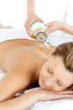 Glad young woman enjoying a back massage with oil. In a spa center stock photo