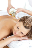 Glad young woman enjoying a back massage with oil. In a spa center royalty free stock photos
