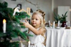 glada lyckliga ferier för jul Den gulliga lilla flickan dekorerar en julgran Arkivbilder