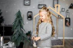 glada lyckliga ferier för jul Den gulliga lilla flickan dekorerar en julgran Arkivfoton