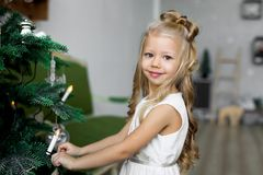 glada lyckliga ferier för jul Den gulliga lilla flickan dekorerar en julgran Arkivfoto