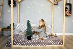 glada lyckliga ferier för jul Den gulliga lilla flickan dekorerar en julgran Royaltyfri Fotografi