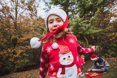 glada lyckliga ferier för jul Den nätta flickan i röd tröja och julhatt har gyckel, och hennes familj dekorerar en jultre royaltyfria foton