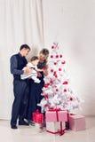 glada lyckliga ferier för jul Föräldrar och behandla som ett barn flickan som har roligt och tillsammans inomhus spelar nära julg Arkivbild