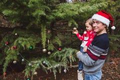 glada lyckliga ferier för jul Fader i röd jul hatt och dotter i röd tröja som dekorerar den utomhus- julgranen arkivfoto