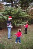glada lyckliga ferier för jul Fader i röd julhatt och två döttrar i röda tröjor som dekorerar julgranouen royaltyfri bild