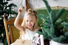 glada lyckliga ferier för jul Gladlynt gullig barnflicka som öppnar en julklapp Arkivbild