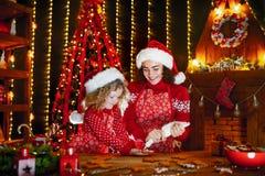 glada lyckliga ferier för jul Gladlynt gullig lockig liten flicka och hennes äldre syster, i att laga mat för santas hattar arkivfoton