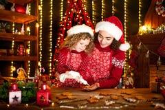 glada lyckliga ferier för jul Gladlynt gullig lockig liten flicka och hennes äldre syster, i att laga mat för santas hattar royaltyfria bilder