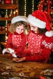 glada lyckliga ferier för jul Gladlynt gullig lockig liten flicka och hennes äldre syster, i att laga mat för santas hattar royaltyfri foto