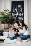 glada lyckliga ferier för jul Gladlynt mamma och hennes gullig dotterflicka som öppnar en julklapp Förälder och Royaltyfri Foto