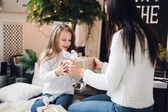 glada lyckliga ferier för jul Gladlynt mamma och hennes gullig dotterflicka som öppnar en julklapp Förälder och Fotografering för Bildbyråer