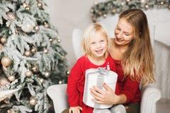 glada lyckliga ferier för jul Gladlynt mamma och hennes gullig dotterflicka som utbyter gåvor Royaltyfria Bilder