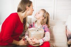 glada lyckliga ferier för jul Gladlynt mamma och hennes gullig dotterflicka som utbyter gåvor arkivbild