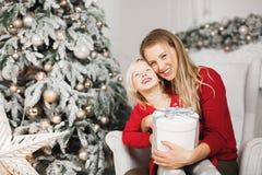 glada lyckliga ferier för jul Gladlynt mamma och hennes gullig dotterflicka som utbyter gåvor royaltyfri fotografi