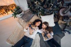 glada lyckliga ferier för jul Gladlynt mamma och hennes gullig dotterflicka som utbyter gåvor Förälder och litet barn Arkivfoto