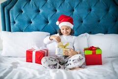 glada lyckliga ferier för jul Julklappar, unge och feriebegrepp Den härliga flickan öppnar en julgåva från jultomten Arkivbild