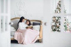 glada lyckliga ferier för jul Nätt ung mamma som inomhus läser en bok till hennes gulliga dotter nära julgranen Fotografering för Bildbyråer
