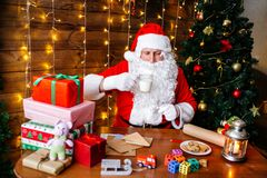 glada lyckliga ferier för jul Santa Claus förbereder gåvor för barn för Xmas på skrivbordet hemma royaltyfria foton