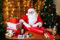 glada lyckliga ferier för jul Santa Claus förbereder gåvor för barn för Xmas på skrivbordet hemma royaltyfri bild