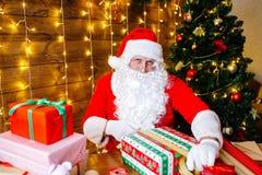 glada lyckliga ferier för jul Santa Claus förbereder gåvor för barn för Xmas på skrivbordet hemma royaltyfria bilder