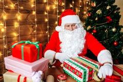 glada lyckliga ferier för jul Santa Claus förbereder gåvor för barn för Xmas på skrivbordet hemma royaltyfri fotografi
