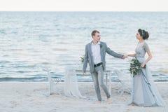 Gladde nyligen gift parinnehavhänder vid havet Arkivfoton