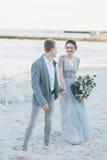 Gladde nyligen gift parinnehavhänder vid havet Royaltyfri Foto