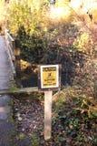 Gladde voorzichtigheid wanneer nat of ijzig teken in het al Bos stock foto's