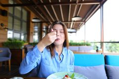Satisfied girl eating dessert at restaurant  . Gladden female customer eating dessert at restaurant   with satisfied smile. Charming girl enjoying having lunch Stock Photo