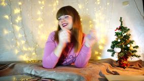 Gladden teenager listening to New Year songs. Cheerful girl raving alone in cozy twinkling room. Jocund female person smiling and enjoying winter holidays stock footage