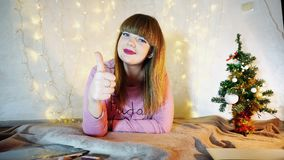 Gladden teenager listening to New Year songs. Cheerful girl raving alone in cozy twinkling room. Jocund female person smiling and enjoying winter holidays Royalty Free Stock Photo