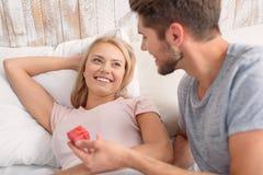 Glade älska par som firar i sovrum arkivfoto