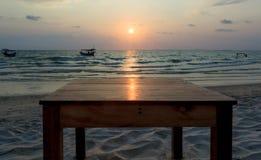 Glade Солнця na górze деревянного стола на заходе солнца с предпосылкой вида на море Стоковые Изображения RF