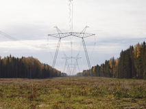 Glade  in the autumn forest with the supports of power lines. Royalty Free Stock Photos