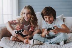 Glade barn med modiga kontrollanter spelar videospel hemma Arkivfoto