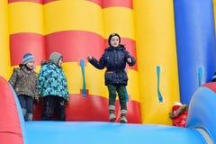 Glade barn rider på uppblåsbar färgrik glidbana i formnollan Arkivbilder