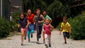 Glade barn som körs längs vägen arkivfilmer