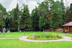 Glade with cobbled paving paths and beautiful flower bed. And green trees Royalty Free Stock Photography