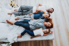 Glade föräldrar med deras ungar som lägger på säng royaltyfri foto