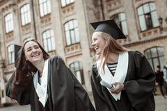 Glade flickor som har gyckel, medan stå nära universitet arkivfoto